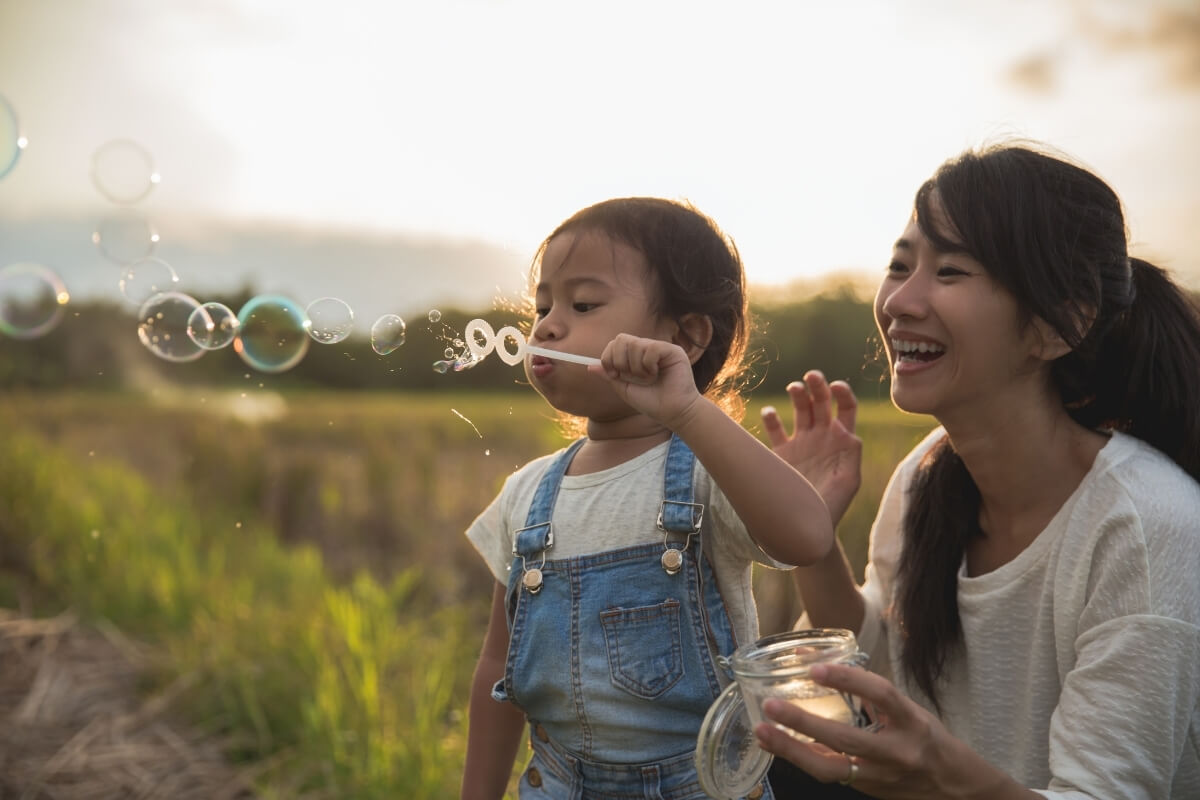 asian mum and child playing bubbles