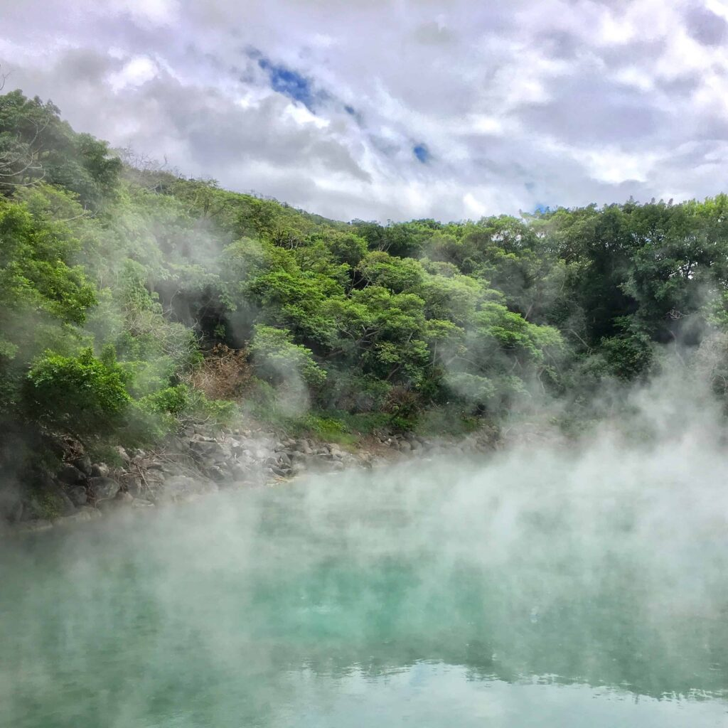 Beitou Hell Valley. Steaming hot spring with green mountain backdrop and fluffy white clouds in blue sky