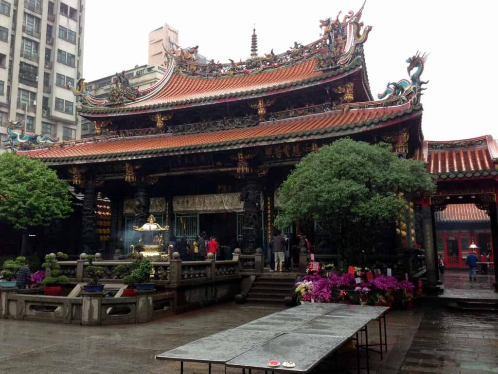 Longshan temple in Taipei, Taiwan. Asian temple with double level roof. Trees on left and right of the temple entrance. Grey tables in front of the trees.